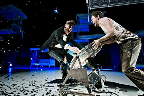 Florian Steffens wird von Maximilian Scheidt auf einem großen Ventilator in Zeitlupe durch den Raum geschoben.