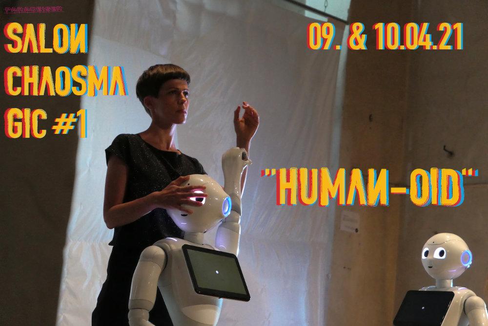 Eine Frau (Eva-Maria Kraft) steht hinter einem Roboter, ein zweiter schaut die beiden an. Szenenfoto aus einer Performance.