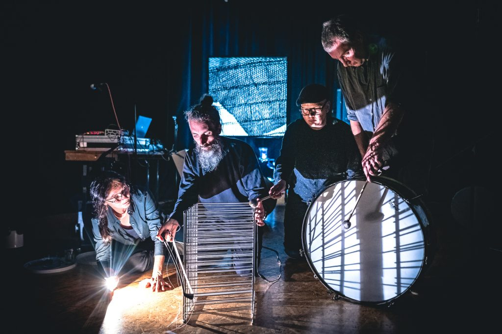 vier menschen bearbeiten ungewöhnliche Klangerzeuger. Dazu gibt es licht und schatten