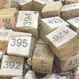 Pflastersteine mit Nummern liegen scheinbar unsortiert auf einem Haufen
