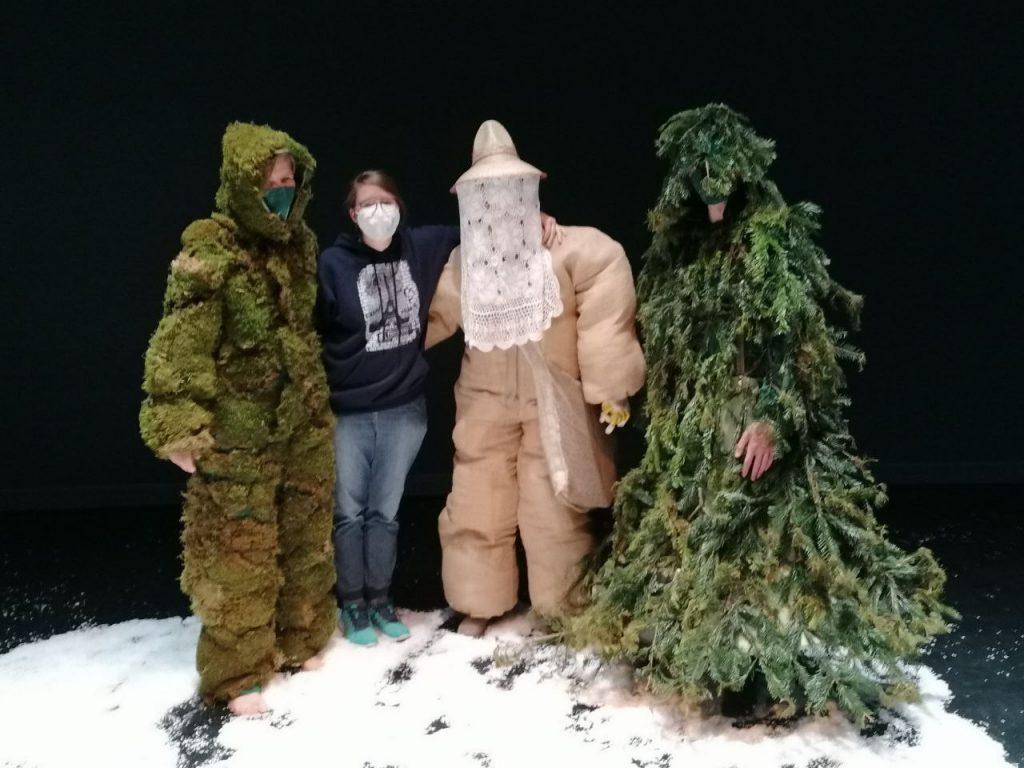 """drei seltsame Kostüme (Moos, Tanne, Imkerin) und die Ausstatterin (mit Atemschutzmaske) stehen in künstlichem Schnee auf der Bühne von """"Denkraum der Utopien"""" nach der letzten Vorstellung."""