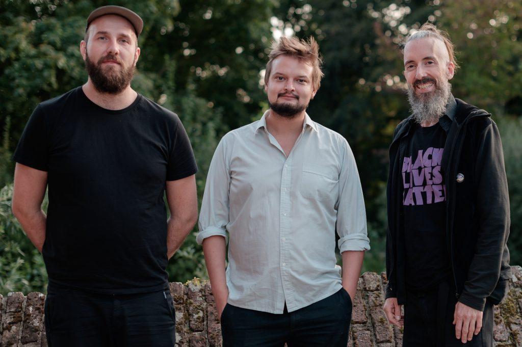 Marvin Blamberg, Moritz Anthes, Kai Niggemann stehen vor einem grünen Hintergrund im Park von Schloß RIngenberg